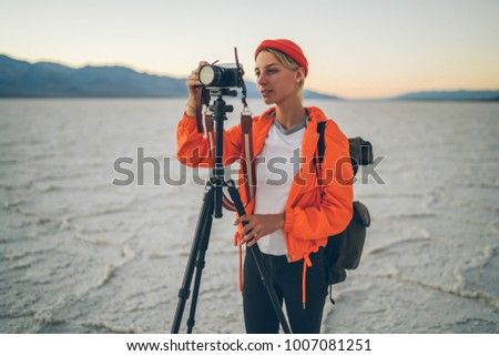 Professional female photographer making picture of beautiful landscape in Death Valley using camera and tripod, skilled traveler blogger shooting video of unique landscape of dry lake in national park