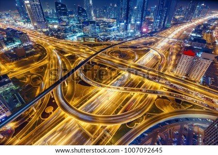 Aerial view of big highway interchange with traffic in Dubai, UAE, at night. Scenic cityscape. Colorful transportation, communications and driving background. #1007092645
