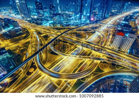 Aerial view of big highway interchange with traffic in Dubai, UAE, at night. Scenic cityscape. Colorful transportation, communications and driving background. #1007092885