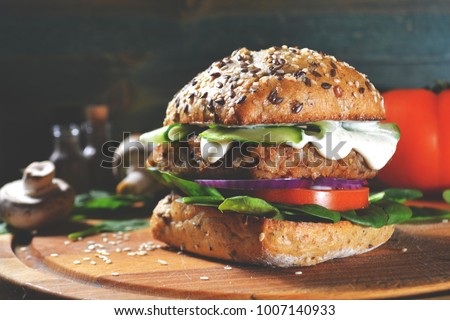 veggie, vegan burger with buckwheat, tomato, onion, vegan mayonnaise and spinach on a fresh bun with flax seeds and sesame, surrounded by spinach leaves, mushrooms, tomato, black pepper and spices. #1007140933
