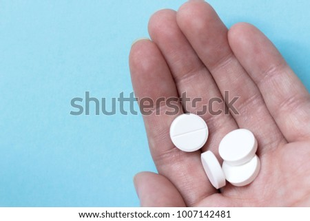Female hand whire circle pills. Blue background. Medications. Concept medicine #1007142481
