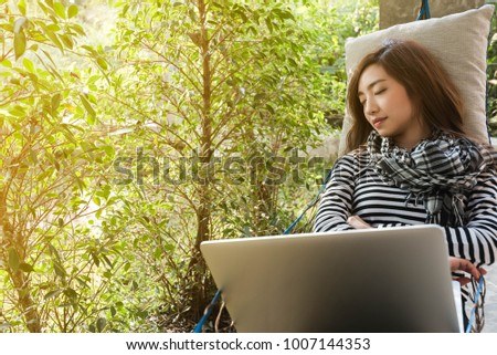 Young woman sleeping in hammock while use laptop, freelance life style conceptual, work anywhere #1007144353