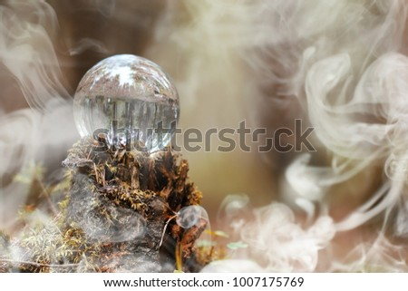 A crystal ball in the smoke. A magical accessory in the woods on the stump. Ritual ball of witches and sorcerers on an old rotten stump. #1007175769