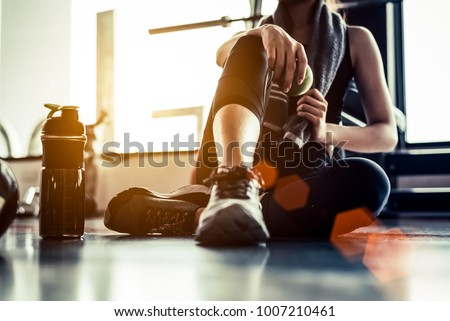 Sport woman sitting and resting after workout or exercise in fitness gym with protein shake or drinking water on floor. Relax concept. Strength training and Body build up theme. Warm and cool tone  #1007210461