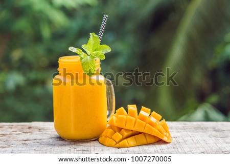 Mango smoothie in a glass Mason jar and mango on a green background. Mango shake. Tropical fruit concept. #1007270005