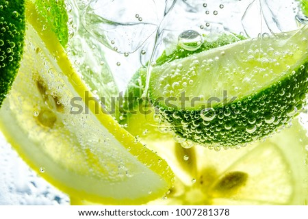 Lemon slice drop in fizzy sparkling water, juice refreshment Royalty-Free Stock Photo #1007281378