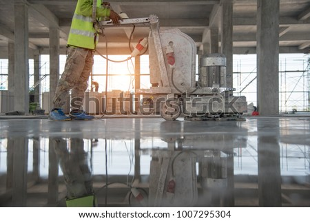 Construction worker produces the grout and finish wet concrete with a special tool. Float blades. For smoothing and polishing concrete, concrete floors #1007295304