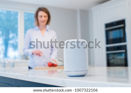 Woman Working In Kitchen With Smart Speaker In Foreground #1007322106