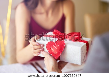 Valentine's Day concept. Happy couple in love with. A young loving couple celebrating Valentine's Day in the restaurant. Lovers give each other gifts. Romance restaurant for Valentine's Day- concept #1007330647