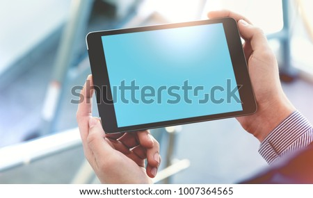 Mock up of a man holding digital tablet device in hands. Clipping path #1007364565