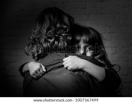 Photo shooting indoors. On the background of a white brick wall . Child ( girl ) hugs his mother.  #1007367499