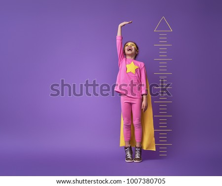 Little child is playing superhero. Kid is measuring the growth on the background of bright ultraviolet wall. Girl power concept. Yellow, pink and  purple colors. #1007380705