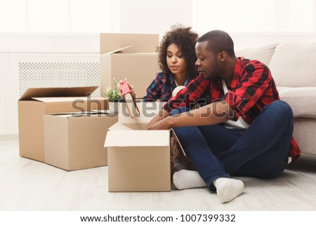 Happy african-american couple unpacking moving boxes and taking out books in new apartment, copy space #1007399332