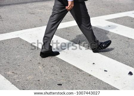 Man in suite walking in the street passing the zebra #1007443027