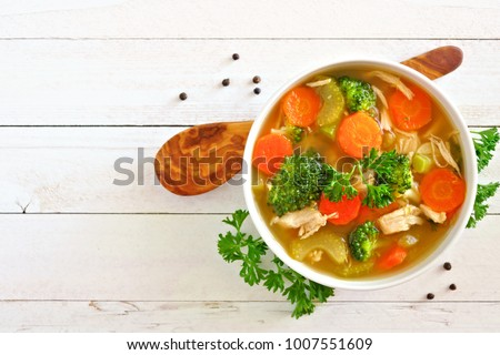 Homemade chicken vegetable soup, overhead view on a white wood background #1007551609