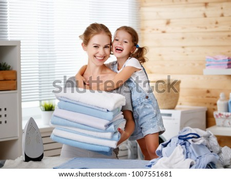 Happy family mother housewife and child daughter  ironing clothes iron in laundry at home #1007551681