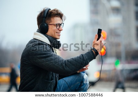 Happy attractive young man in headset taking selfie on his mobile phone, walking on the street of city. Dressed in warm jacket and jeans, in eyeglasses. #1007588446