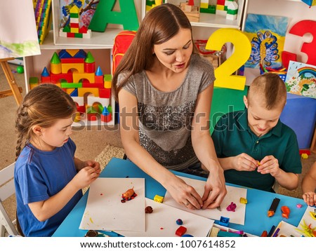 Plasticine modeling clay in children class. Teacher teaches kids together play dough and mold from plasticine in kindergarten or preschool. Educational childhood play room. #1007614852