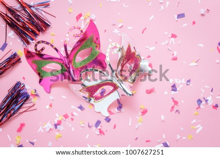 Flat lay aerial image of beautiful purple silver carnival mask for carnaval holiday background concept. Table top view object on modern rustic pink paper at home office desk studio.space for creative