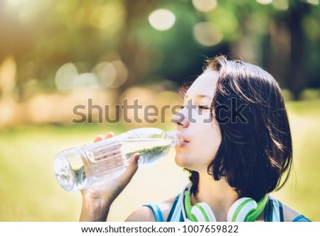 A girl drinking water with thirst after exercise, with a park in the background. #1007659822