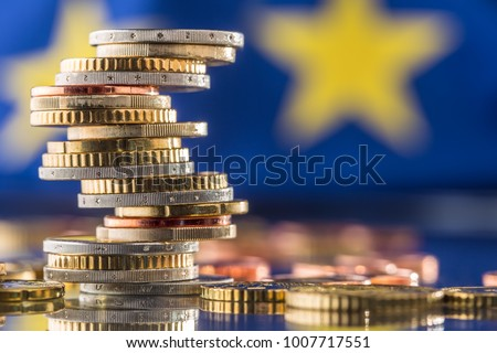 Tower with euro coins and flag of European Union in the background. #1007717551