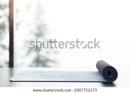 Yoga mat on the floor near big window with beautiful landscape with winter trees and mountains #1007752273
