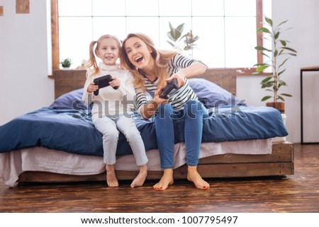 Mother. Lovely happy fair-haired girl laughing and holding a remote control playing with her mom while sitting on the bed #1007795497