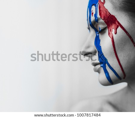Paint on the female face, close-up. Flows of red and blue paint on the face. Artistic portrait of a hard face in paint. Black and white photos face in paint. #1007817484