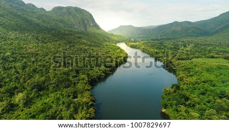 Beautiful natural scenery of river in southeast Asia tropical green forest  with mountains in background, aerial view drone shot #1007829697