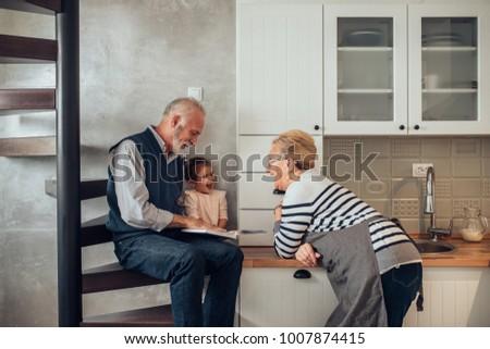 Elderly couple reading stories ti their granddaughter #1007874415