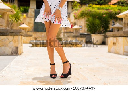Woman with slim sexy legs posing in white summer dress and black high heels #1007874439