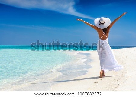 Happy traveller woman in white dress enjoys her tropical beach vacation Royalty-Free Stock Photo #1007882572