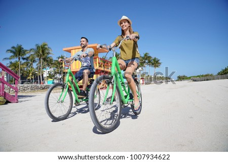 Couple of tourists riding bike in Miami beach #1007934622
