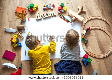 Preschool boy and girl play on floor with educational toys - blocks, train, railroad, plane. Toddler kids drawing. Toys for preschool and kindergarten. Children at  home or daycare. Top view #1008016099