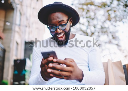 Emotional surprised african american guy with low prices in web store receiving message with promo code,excited dark skinned hipster guy in trendy hat overjoyed with winning online contest on web site #1008032857