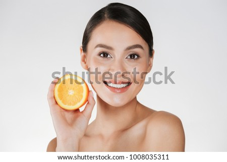 Close up image of satisfied woman with healthy fresh skin holding juicy orange and smiling isolated over white background #1008035311