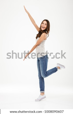 Full length image of Cheerful brunette woman presenting copyspace and looking at the camera over gray background