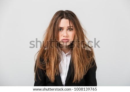 Portrait of an exhausted businesswoman dressed in suit with messy hair looking at camera isolated over gray background Royalty-Free Stock Photo #1008139765