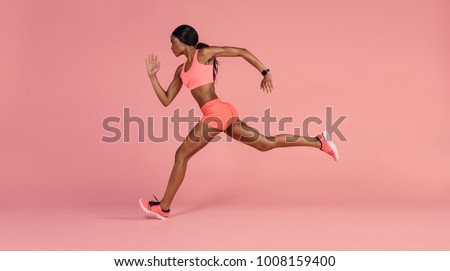 Fit and healthy woman running. African female runner sprinting on pink background.