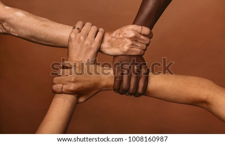 Four diverse women holding each others wrists in a circle. Top view of female hands linked in the lock against brown background. #1008160987