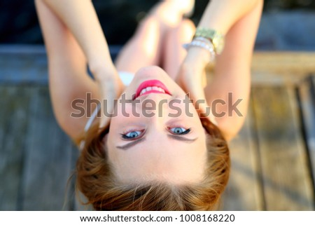 Upside down portrait of young woman with bright blue eyes and red hair. Unusual view from top on ginger girl face. #1008168220