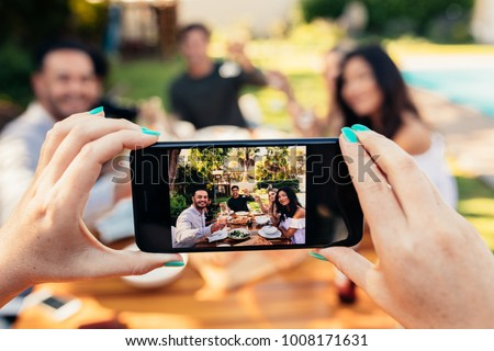 Young people having fun outdoors. Group of friends posing while their friend take a picture with his smart phone. Female hands taking picture of friends having party.