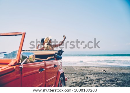 Romantica couple making photo on smartphone camera standing near vintage rental car on ocean beach enjoying summer vacation together, hipsters taking picture on cellular resting near sea on weekends #1008189283