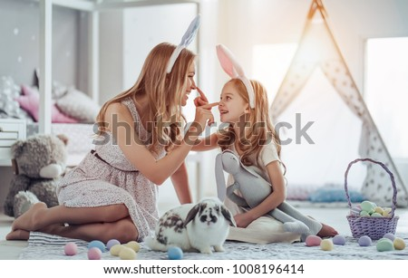 Attractive young woman with little cute girl are preparing for Easter celebration. Mom and daughter wearing bunny ears are having fun with Easter bunny while sitting on the floor at home. #1008196414