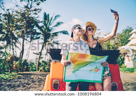Romantic couple making selfie on mobile phone camera posing near vintage rental automobile traveling during honeymoon,positive girl in hat making photo with her boyfriend reading map during roadtrip