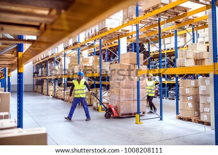 Warehouse workers pulling a pallet truck. #1008208111