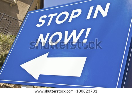 Blue Sign with an arrow reading stop in now.