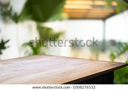 empty wood desk over blurred montage coffee shop cafe / restaurant background