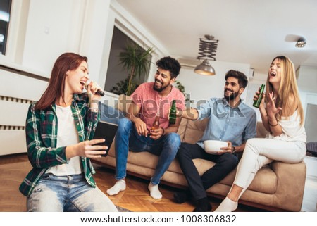 Group of friends playing karaoke at home. Concept about friendship, home entertainment and people #1008306832