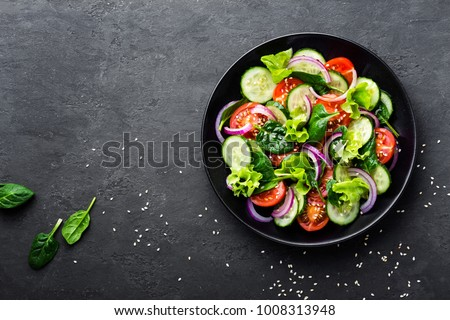 Healthy vegetable salad of fresh tomato, cucumber, onion, spinach, lettuce and sesame on plate. Diet menu. Top view. #1008313948